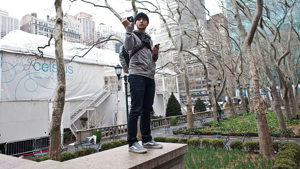 Tim Pool, an independent reporter uses his cell phone to broadcast live stream on the internet during a day of action with the Occupy Wall Street movement in New York, on Wednesday, February 29, 2012. (Photo by Ramin Talaie/Corbis via Getty Images)