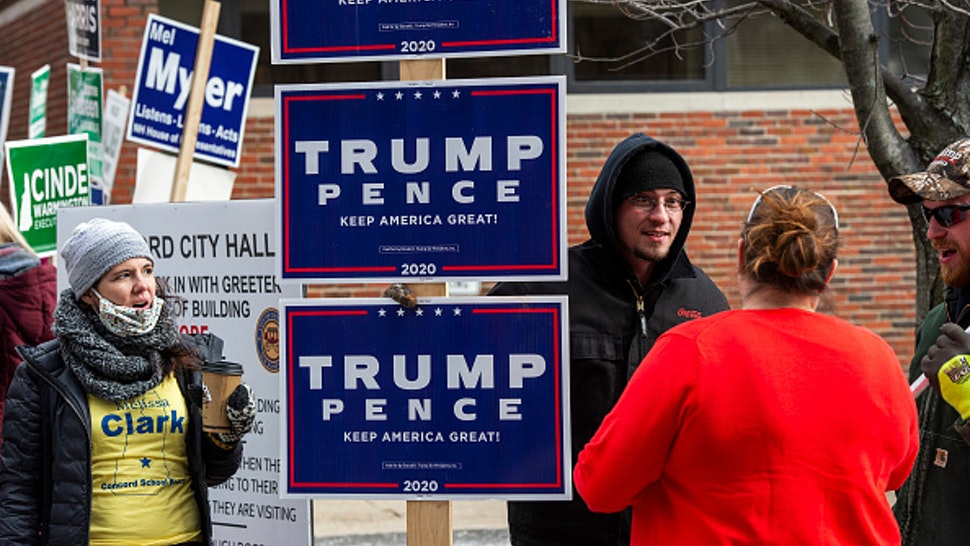 A woman brings coffee to sign holders outside a polling station on Election Day in Concord, New Hampshire on November 3, 2020. - Americans were voting on Tuesday under the shadow of a surging coronavirus pandemic to decide whether to reelect Republican Donald Trump, one of the most polarizing presidents in US history, or send Democrat Joe Biden to the White House
