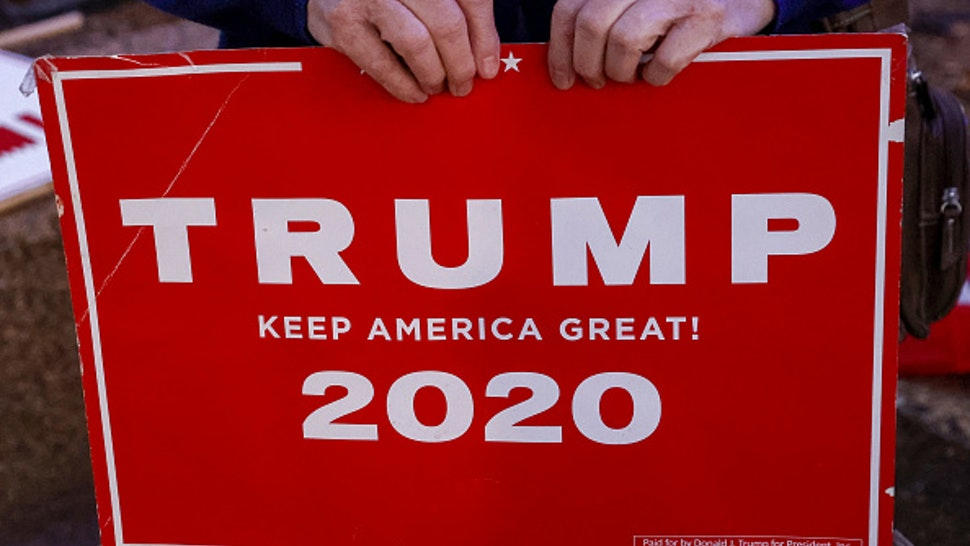 An Israeli supporter of US President Donald Trump carries a sign during a rally in the northern Israeli city of Karmiel near Haifa on November 3, 2020, to express their support for him during the US presidential election.