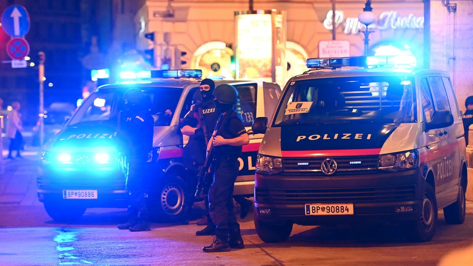 """Police cars and policemen stand in the central Vienna on November 2, 2020, following a shooting near a synagogue. - Multiple gunshots were fired in central Vienna on the evening of November 2, 2020, according to police, with the location of the incident close to a major synagogue. Police urged residents to keep away from all public places or public transport. One attacker was """"dead"""" and another """"on the run"""", with one police officer being seriously injured, Austria's interior ministry said according to news agency APA."""