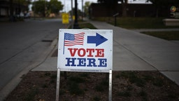 """MINNEAPOLIS, MN - AUGUST 14: A sign reading """"Vote Here"""" points toward a polling place for the 2018 Minnesota primary election at Holy Trinity Lutheran Church on August 14, 2018 in Minneapolis, Minnesota"""