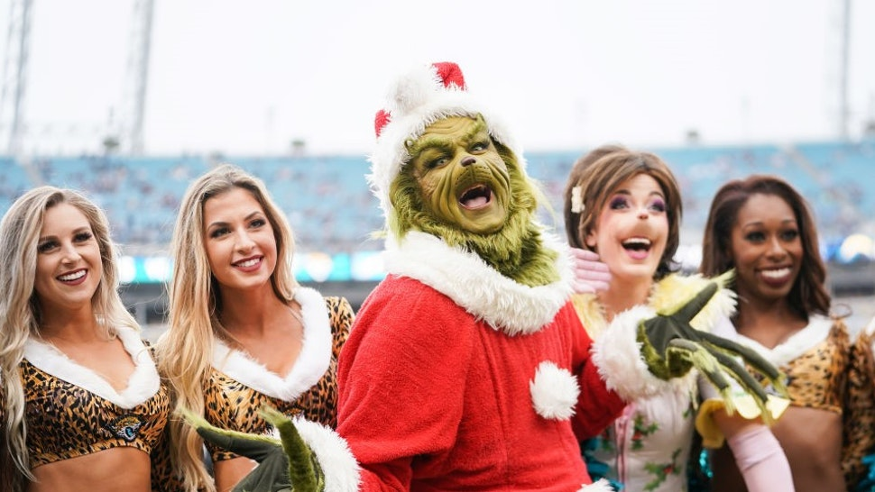 JACKSONVILLE, FLORIDA - DECEMBER 08: The Grinch poses with cheerleaders from the Jacksonville Jaguars before the start of a game against the Los Angeles Chargers at TIAA Bank Field on December 08, 2019 in Jacksonville, Florida. (Photo by