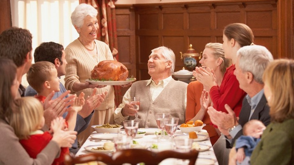 Grandmother presenting turkey to her family at the dinner table
