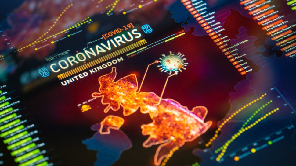 Coronavirus (COVID-19) Outbreak in United Kingdom Statistics close-up on digital display.