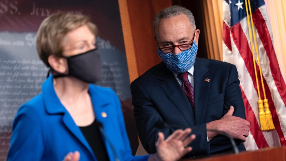 Senate Minority Leader Chuck Schumer (D-NY) (R) listens as U.S. Sen. Elizabeth Warren (D-MA) speaks during a news conference on Capitol Hill on October 20, 2020 in Washington, DC.