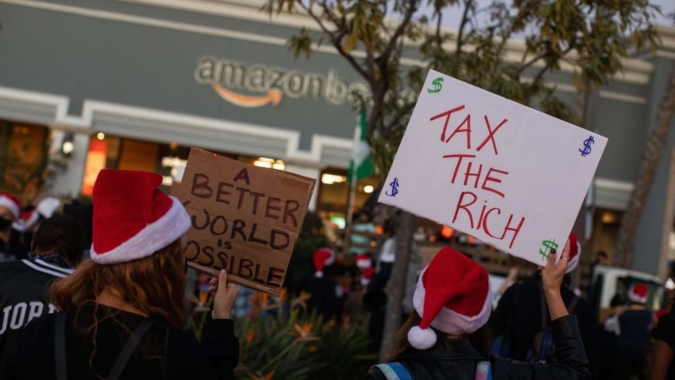 Protesters wearing Santa's hats hold signs as they demonstrate in front of the Amazon Book Store in the Waterside shopping center in the Marina Del Rey neighborhood of Los Angeles during a Black Lives Matter rally to demand social justice on December 19, 2020.