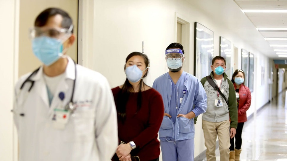 DALY CITY, CA - DEC. 21: Donning a mask and face shield, Roman Romo, center, waits in line with other staff members to receive a coronavirus vaccine at Seton Medical Center on Monday, December 21, 2020, in Daly City, California.