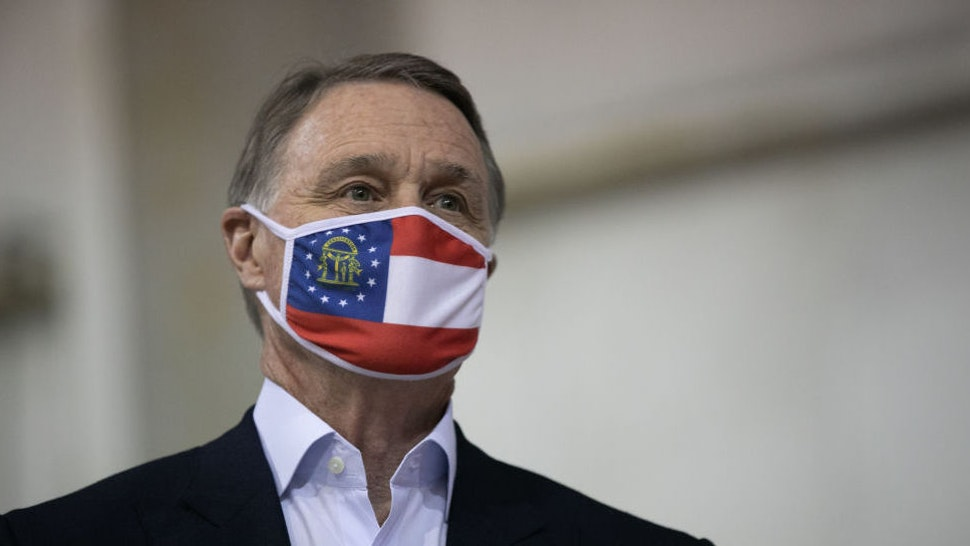 ATLANTA, GA - DECEMBER 14: Sen. David Perdue (R-GA) looks on during a campaign rally at Peachtree Dekalb Airport on December 14, 2020 in Atlanta, Georgia. As early voting begins, Perdue is facing Democratic candidate Jon Ossoff in a runoff election. The results of two Georgia Senate races will determine the party that controls the majority in the U.S. Senate.