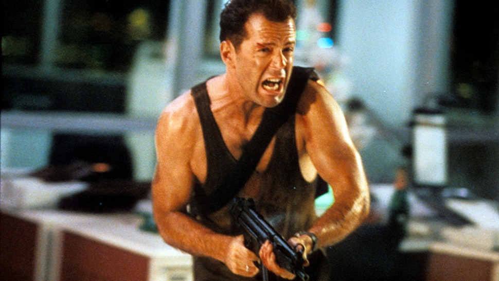 Bruce Willis running with automatic weapon in a scene from the film 'Die Hard', 1988.