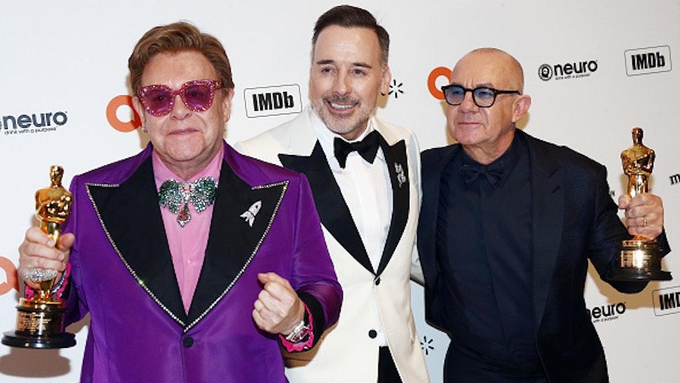 LOS ANGELES, CALIFORNIA - FEBRUARY 09: Elton John, David Furnish and Bernie Taupin walk the red carpet at the Elton John AIDS Foundation Academy Awards Viewing Party on February 09, 2020 in Los Angeles, California.