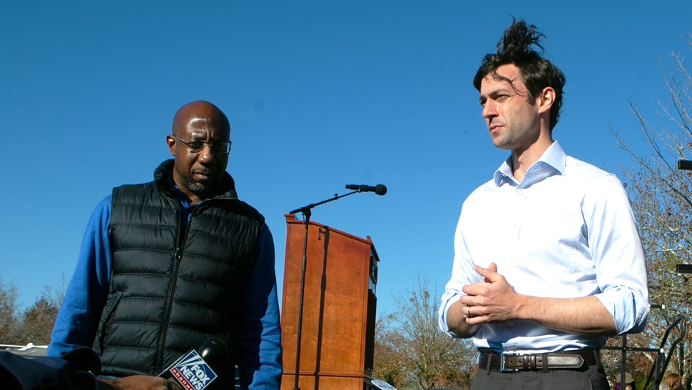 CONYERS, GA - DECEMBER 05: Democratic U.S. Senate candidates Raphael Warnock (L) and Jon Ossoff take questions from the press during an outdoor drive-in rally on December 5, 2020 in Conyers, Georgia. Ossoff and Warnock face Republican candidates Sen. David Purdue (R-GA) and Sen. Kelly Loeffler in a runoff election that will take place January 5th.