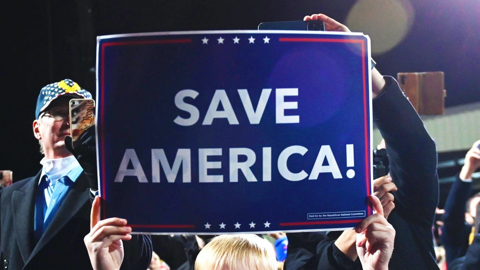 "A boy holds a ""Save America"" sign as US president Donald Trump speaks at a rally to support Republican Senate candidates at Valdosta Regional Airport in Valdosta, Georgia on December 5, 2020. - President Donald Trump ventures out of Washington on Saturday for his first political appearance since his election defeat to Joe Biden, campaigning in Georgia where two run-off races will decide the fate of the US Senate."