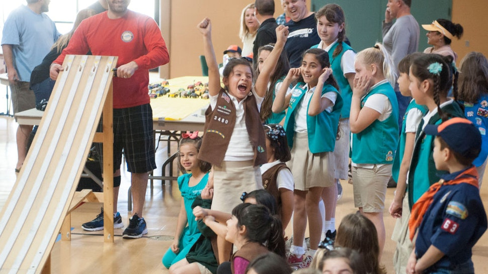 Starter Elyas Balta, at left, smiles as a Girl Scout celebrates an early victory at the combined Cub Scout/Girl Scout Pinewood Derby races at St. Norbert Catholic School in Orange Saturday.