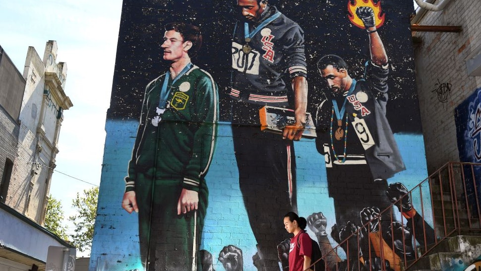 A photo taken in Melbourne on October 8, 2018, shows a man walking past a giant mural of Australian runner Peter Norman with US sprinters Tommie Smith and John Carlos.