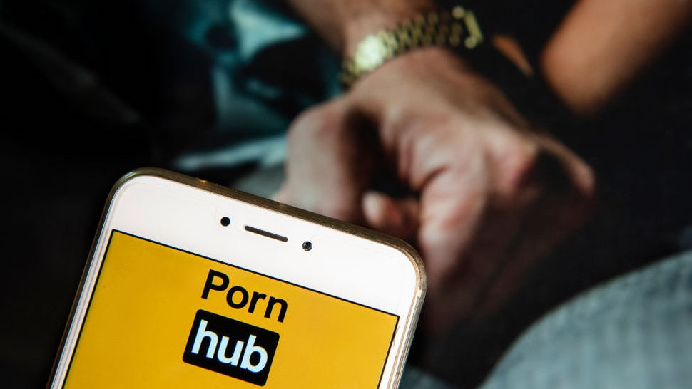 In this photo illustration, the Pornographic video sharing website Pornhub logo is seen displayed on an Android mobile device with a couple holding hands image in the background.