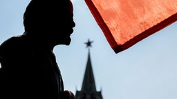 TOPSHOT - A red flag is seen above a bust of the Soviet state founder and revolutionary leader Vladimir Ilyich Ulyanov aka Lenin as Russian Communist party members and supporters attend a flower-laying ceremony marking the 149th anniversary of his birth, on Red Square in Moscow, April 22, 2019.