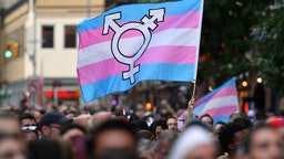 A person holds a transgender pride flag as people gather on Christopher Street outside the Stonewall Inn for a rally to mark the 50th anniversary of the Stonewall Riots in New York, June 28, 2019. - The June 1969 riots, sparked by repeated police raids on the Stonewall Inn -- a well-known gay bar in New York's Greenwich Village -- proved to be a turning point in the LGBTQ community's struggle for civil rights.