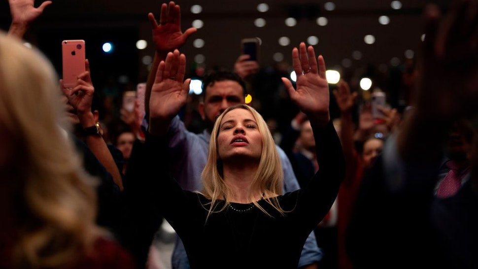 TOPSHOT - Supporters pray as US President Donald Trump speaks during a 'Evangelicals for Trump' campaign event held at the King Jesus International Ministry on January 03, 2020 in Miami, Florida. (Photo by JIM WATSON / AFP) (Photo by JIM WATSON/AFP via Getty Images)