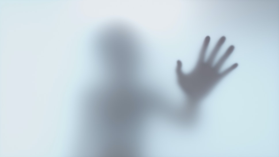 Shadow hands of woman behind frosted glass
