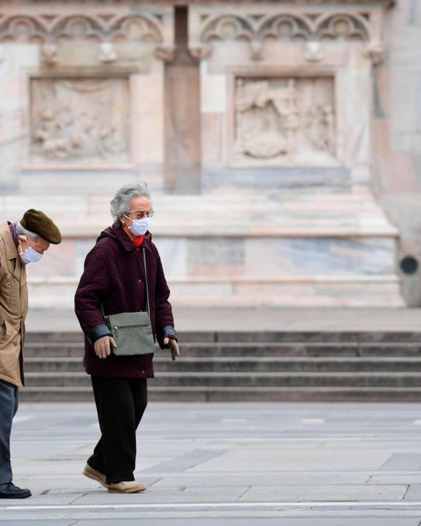 An elderly couple wearing protective masks walk across a deserted Duomo square in Milan on March 31, 2020, during the country's lockdown aimed at curbing the spread of the COVID-19 infection, caused by the novel coronavirus. (Photo by MIGUEL MEDINA / AFP) (Photo by MIGUEL MEDINA/AFP via Getty Images)