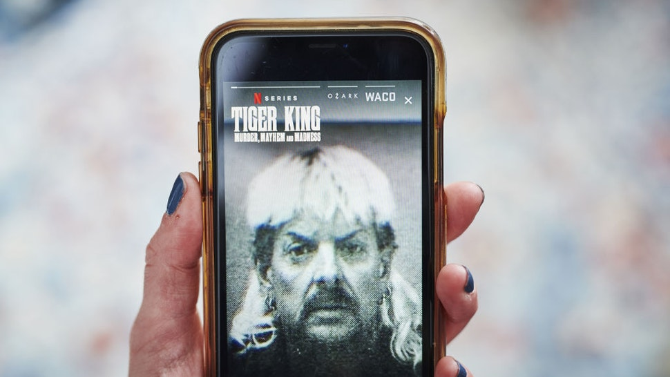 """The Netflix Inc. true crime documentary miniseries """"Tiger King"""" trailer is displayed on a smartphone in an arranged photograph taken in the Brooklyn Borough of New York, U.S., on Monday, April 20, 2020. Netflix Inc. is riding a wave of optimism as it heads into its earnings report Tuesday, with investors pushing the shares tonew highsand analysts seeing people download its app in record numbers. Photographer: Gabby Jones/Bloomberg via Getty Images"""