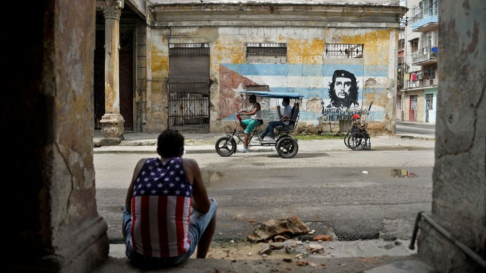 Man wearing a tank top with a design of the US flag rests in Havana on October 21, 2020, amid the COVID-19 novel coronavirus pandemic.
