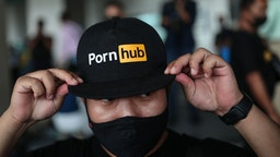 A protester wears a cap with the Pornhub logo during a demonstration at the Ministry of Digital Economy and Society in Bangkok on November 3, 2020, after the website was blocked by the ministry. (Photo by Jack TAYLOR / AFP) (Photo by JACK TAYLOR/AFP via Getty Images)