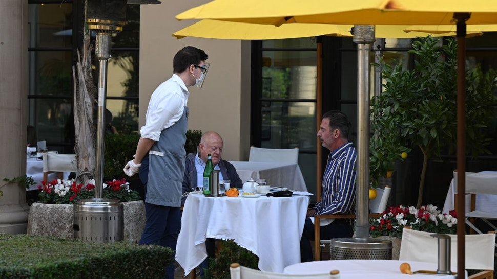 A server wearing a mask and face shield takes orders from customers at a restaurant in Beverly Hills, California, November 23, 2020. - Los Angeles County pubic health officials have issued an order to suspend all restaurant dining including outdoor dining for three weeks, starting November 24 at 10pm amid a surge of new coronavirus cases. There is major pushback against the order which some estimates will result in the loss of 700,000 jobs and lead to the closure of restaurants. (Photo by Robyn Beck / AFP) (Photo by ROBYN BECK/AFP via Getty Images)