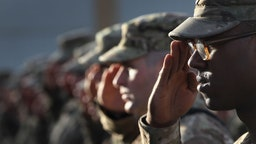 BAGRAM, AFGHANISTAN - SEPTEMBER 11: U.S. Army soldiers salute during the national anthem during the an anniversary ceremony of the terrorist attacks on September 11, 2001 on September 11, 2011 at Bagram Air Field, Afghanistan. Ten years after the 9/11 attacks in the United States and after almost a decade war in Afghanistan, American soldiers paid their respects in a solemn observence of the tragic day.