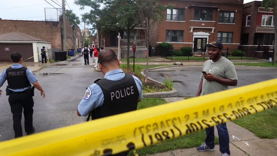 CHICAGO, ILLINOIS - JULY 21: Police secure the scene of a shooting in the Auburn Gresham neighborhood on July 21, 2020 in Chicago, Illinois. At least 14 people were transported to area hospitals after several gunmen opened fire on mourners standing outside of a funeral home. More than 2000 people have been shot and more than 400 have been murdered in Chicago so far this year. (Photo by Scott Olson/Getty Images)
