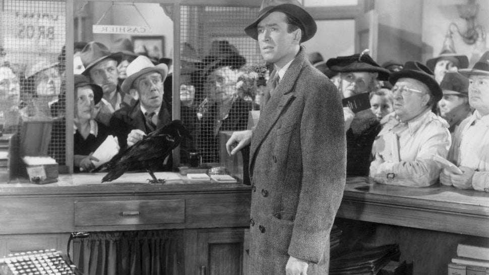 1946: American actor James Stewart (1908 - 1997) stands in the cashier's cubicle of a bank next to a black crow, while a crowd of people wait in the background, in a still from director Frank Capra's film, 'It's a Wonderful Life'. (Photo by Hulton Archive/Getty Images)