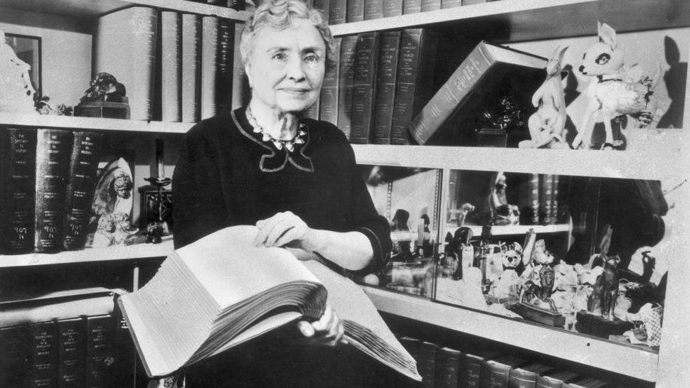 1956: Portrait of American writer, educator and advocate for the disabled Helen Keller (1880 - 1968) holding a Braille volume and surrounded by shelves containing books and decorative figurines. A childhood illness left Keller blind, deaf and mute.