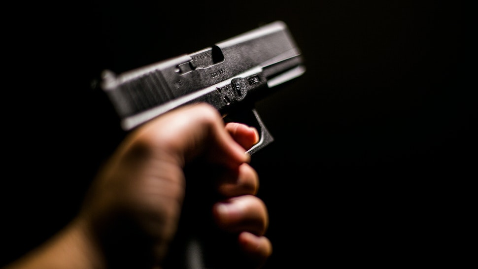 Cropped Hand Holding Gun Against Black Background - stock photo