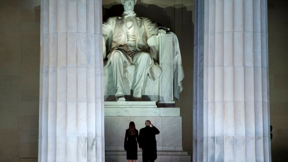 TOPSHOT - US President-elect Donald Trump and wife Melania look at the Abraham Lincoln statue as they arrive for a welcome celebration at the Lincoln Memorial in Washington, DC, on January 19, 2017. (Photo by Brendan Smialowski / AFP) (Photo by BRENDAN SMIALOWSKI/AFP via Getty Images)