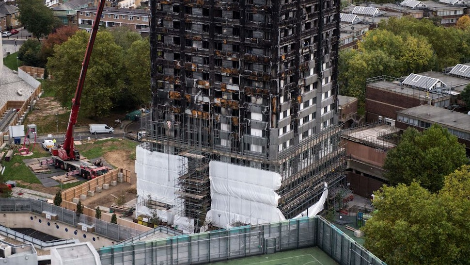 Scaffolding is seen with coverings at the base of the burned-out-shell of Grenfell Tower in London on October 17, 2017 as investigations continue into the tragedy.