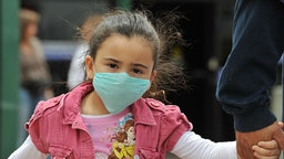 "A girl, wearing a mask, holds her father's hand as they cross the international border between US and Mexico in San Ysidro, California, on April 27, 2009. The World Health Organization (WHO) raised its flu pandemic alert level from three to four, signalling a ""significant increase in risk of a pandemic."" The number of confirmed cases in the United States doubled to 40 on Monday, while Britain and Spain recorded their first swine flu victims. Mexico said the number of confirmed and suspected deaths from the flu had risen to 149, while some 1,600 people were thought to be infected. AFP PHOTO/Jewel SAMAD (Photo credit should read JEWEL SAMAD/AFP via Getty Images)"