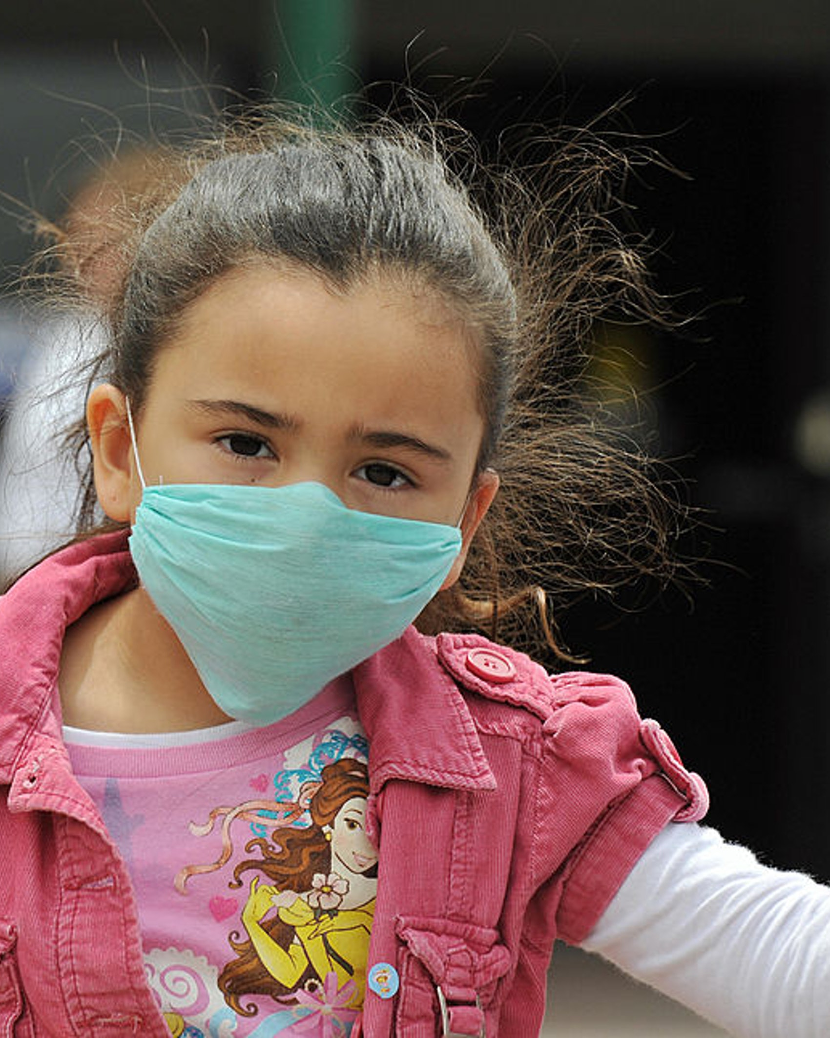 """A girl, wearing a mask, holds her father's hand as they cross the international border between US and Mexico in San Ysidro, California, on April 27, 2009. The World Health Organization (WHO) raised its flu pandemic alert level from three to four, signalling a """"significant increase in risk of a pandemic."""" The number of confirmed cases in the United States doubled to 40 on Monday, while Britain and Spain recorded their first swine flu victims. Mexico said the number of confirmed and suspected deaths from the flu had risen to 149, while some 1,600 people were thought to be infected. AFP PHOTO/Jewel SAMAD (Photo credit should read JEWEL SAMAD/AFP via Getty Images)"""