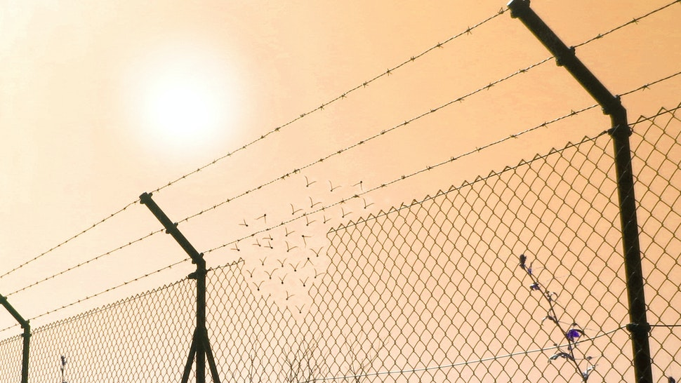Border fence wall against illegal immigration - stock photo