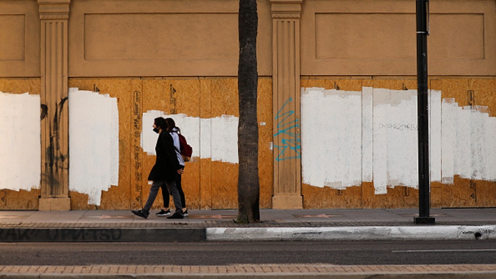 LOS ANGELES, CA - DECEMBER 02: Pedestrians walk past boarded windows of a building on Hollywood Blvd and North Sycamore Ave in Hollywood which is close to Rochelle Begaye, 42, who has created a complex nearby stitched together with plywood, bed frames, and various fencing materials to create a encampment of tents covered with discarded plastic and tarps located on a sliver of land at the corner of Hollywood at La Brea containing the Four Ladies of Hollywood. Hollywood on Wednesday, Dec. 2, 2020 in Los Angeles, CA