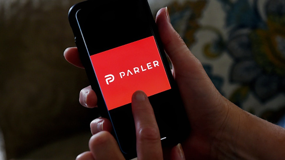 """This illustration picture shows social media application logo from Parler displayed on a smartphone in Arlington, Virginia on July 2, 2020. - Amid rising turmoil in social media, recently formed social network Parler is gaining with prominent political conservatives who claim their voices are being silenced by Silicon Valley giants. Parler, founded in Nevada in 2018, bills itself as an alternative to """"ideological suppression"""" at other social networks."""