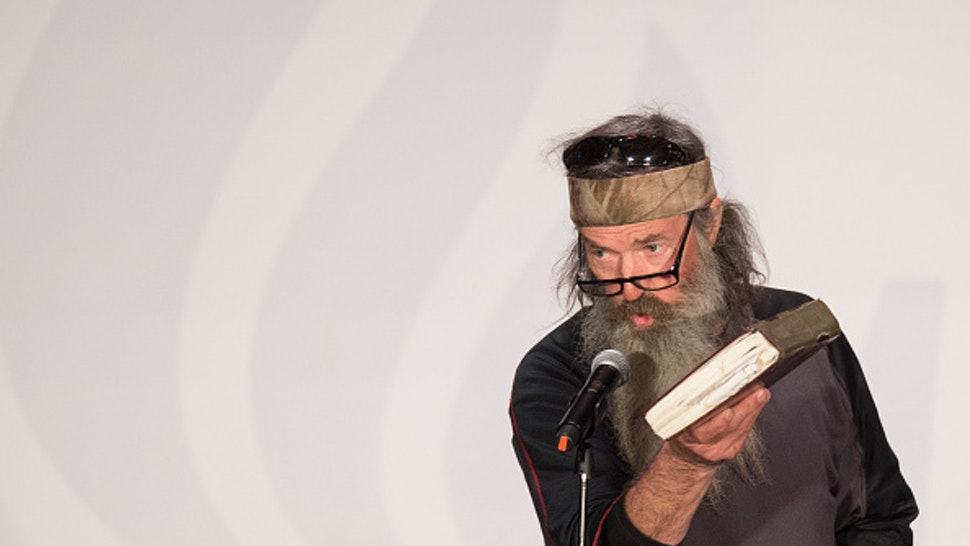 Reality TV's Duck Dynasty star Phil Robertson holds up his Bible during a campaign rally for Republican presidential candidate Ted Cruz in Charleston, South Carolina, February 19, 2016. / AFP / JIM WATSON