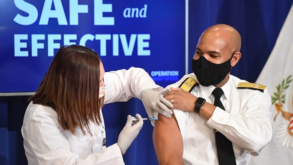 US Surgeon General Jerome Adams receives the COVID-19 vaccine in the Eisenhower Executive Office Building in Washington, DC, December 18, 2020.