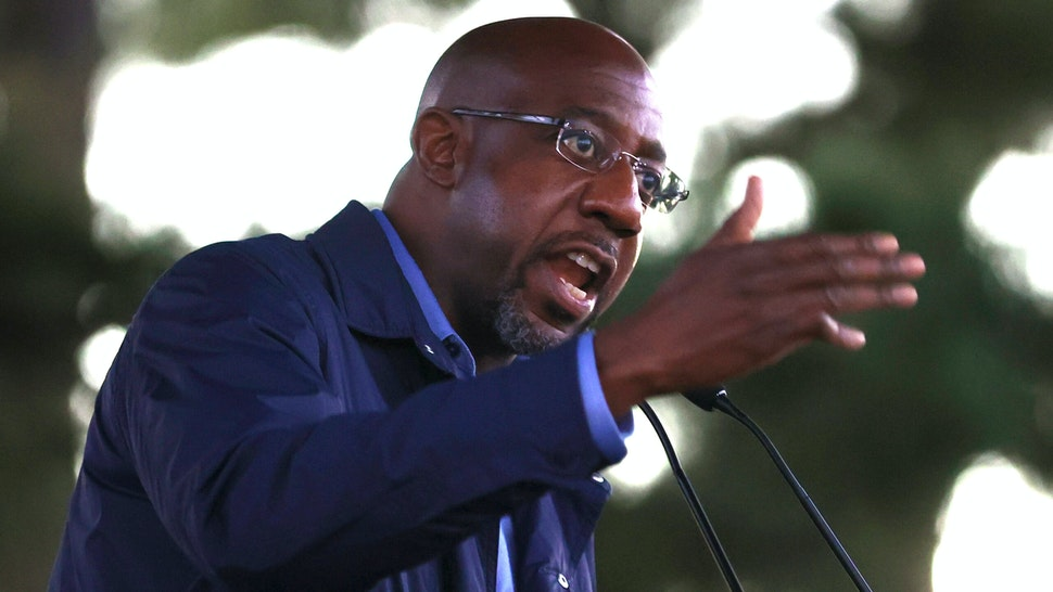 """COLUMBUS, GEORGIA - OCTOBER 29: Democratic U.S. Senate candidate Rev. Raphael Warnock speaks during a """"Get Out the Early Vote"""" drive-in campaign event on October 29, 2020 in Columbus, Georgia. With less than a week to go until Election Day, Democratic candidates for the U.S. Senate in Georgia are continuing to campaign throughout the state."""