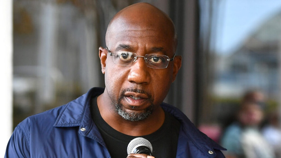ATLANTA, GEORGIA - NOVEMBER 26: Raphael Warnock speaks onstage during Hosea Helps Thanksgiving Dinner Drive Thru at Georgia World Congress Center on November 26, 2020 in Atlanta, Georgia. The annual event was converted into an drive thru outdoor concept due to ongoing COVID-19 pandemic.