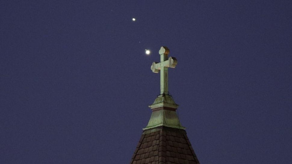 JERSEY CITY, NJ - DECEMBER 18: Saturn and Jupiter set behind a church ahead of their conjunction that is being called The Christmas Star next week on December 18, 2020 in Jersey City, New Jersey. (Photo by