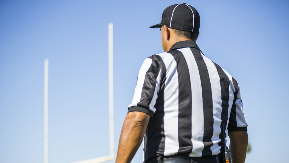 Rear view of football referee wearing black and white striped shirt