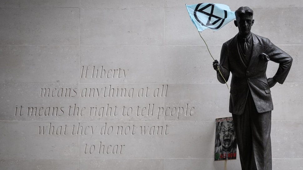 LONDON, ENGLAND - OCTOBER 11: An Extinction Rebellion flag is seen in the hands of a statue of author George Orwell outside the headquarters of the BBC as the environmental group protests about the broadcaster's alleged silence over climate issues on October 11, 2019 in London, England. The Extinction Rebellion group is in the middle of a string of protests across the country, with the aim of highlighting the urgency to address climate change as an ongoing emergency. (Photo by