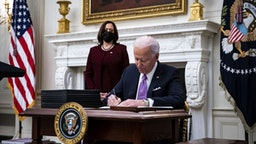 U.S. President Joe Biden signs an executive order after speaking during an event on his administration's Covid-19 response with U.S. Vice President Kamala Harris, left, in the State Dining Room of the White House in Washington, D.C., U.S., on Thursday, Jan. 21, 2021.