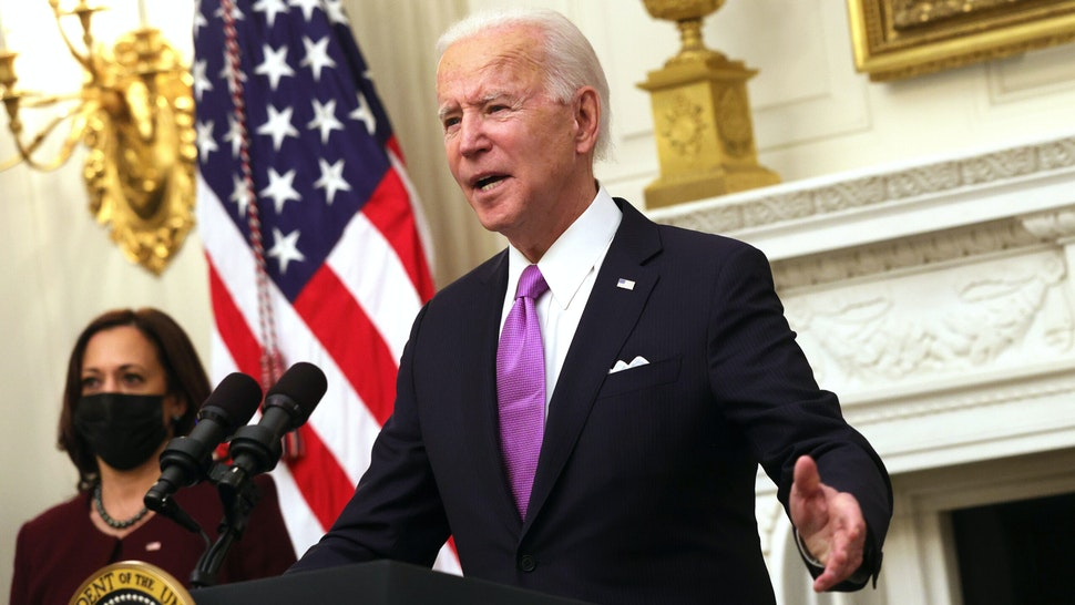 WASHINGTON, DC - JANUARY 21: U.S. President Joe Biden speaks as Vice President Kamala Harris looks on during an event at the State Dining Room of the White House January 21, 2021 in Washington, DC. President Biden delivered remarks on his administration's COVID-19 response, and signed executive orders and other presidential actions.