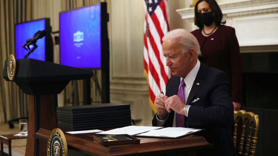 WASHINGTON, DC - JANUARY 21: U.S. President Joe Biden signs executive orders as Vice President Kamala Harris looks on during an event at the State Dining Room of the White House January 21, 2021 in Washington, DC. President Biden delivered remarks on his administration's COVID-19 response, and signed executive orders and other presidential actions.
